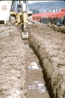 Backhoes and excavation equipment are used to dig the footing for new building construction.