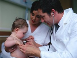A nurse, doctor and newborn baby.