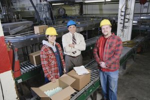 Manager standing beside two employees in warehouse
