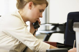 A woman taking notes as she talks on the telephone in an office.