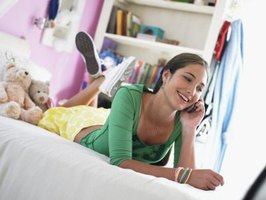 A teen girl talking on the phone in her bedroom.