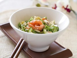 A salmon salad with greens, cucumber, garlic and sesame seeds.