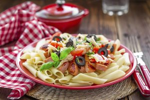 A plate of pasta topped with chicken, tomatoes, olives, cheese and basil.