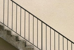 Outdoor stair railings can be made of wood, metal or concrete.