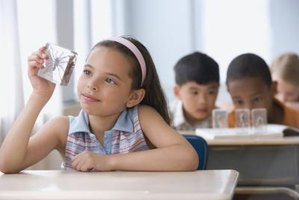 Young student holding up spider specimen in classroom