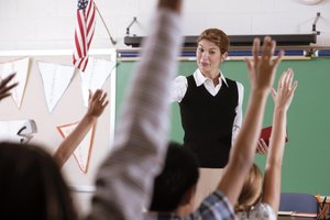Teacher talking in a classroom to students with their hands raised.