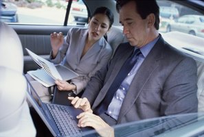 Businessman and businesswoman sitting in back seat of car