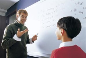 Teacher talking to young student in classroom