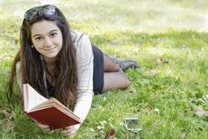 High school student reading book on lawn