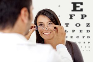 Eye doctor trying glasses on patient