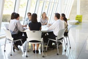 Business professionals have a meeting at a table.