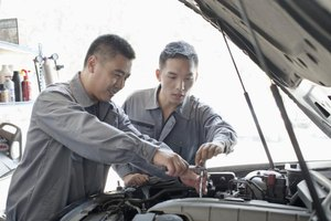 Two mechanics working under the hood of a car.
