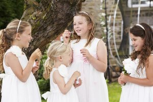 A group of junior bridesmaids blowing bubbles outside.
