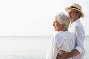 Retired couple embracing by the ocean