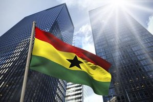 Flag of Ghana in front of two office towers.