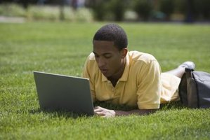 Student working on laptop while lying on grass field