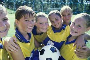 Members of a girls soccer team embrace with a ball.