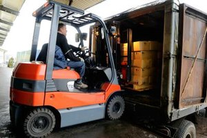 A forklift operator removes boxes from a truck.
