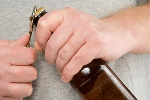 Close-up of hands opening a beer bottle