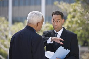 Two businessmen are discussing a letter in their hands.