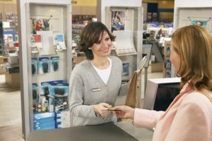 A woman hands a credit card to a cashier in a retail shop