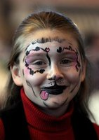 A girl wearing a dog face paint design.