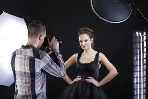 Fashion photographer taking photos of model in studio