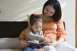 Mother reading a book with daughter.