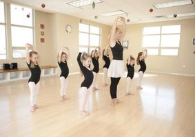 Dance teacher instructing young girls.