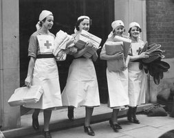 Four British Red Cross nurses carry packages in 1941.
