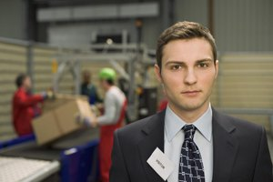 A businessman wearing a visitor's badge in a production facility.