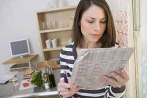 A woman is reading the newspaper.