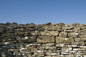 Stacked stone walls can be built as stand-alone walls, or shored up with adhesive.