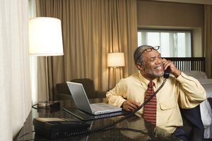A businessman is working from his hotel room.