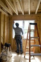 To prevent drafts, rope caulking is pushed into the gap between the window frame and framing studs.