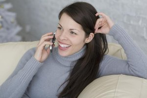 Close-up of woman talking on cell phone at home.