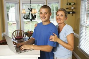 High school boy writing letter on computer with mother's help.