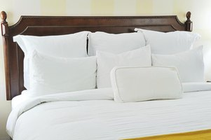 A freshly made bed with white sheets and pillowcases.