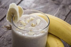 A close-up of a banana smoothie on a table with two fresh bananas.