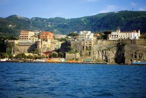 Pastel buildings perch on cliffs over the sea in Sorrento.