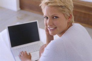 Smiling young woman working on laptop at home
