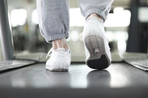 A close-up of a man walking on a treadmill.