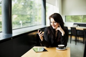 A woman using her smart phone and tablet in a cafe.