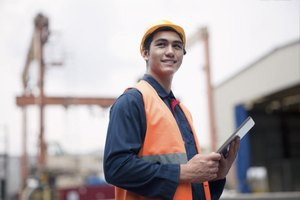 A confident young worker in a shipping yard.