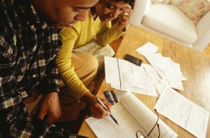A couple looking at an invoice and an accounting ledger on the coffeetable at home.
