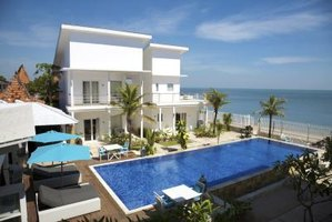 A timeshare property next to a pool overlooking the beach and ocean.