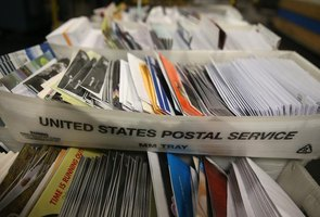 Boxes of mail sit on a cart at a US Post Office
