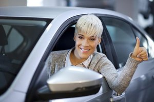 "A young woman sitting in a new car giving a ""thumbs up""."