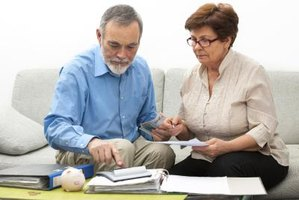 An elderly couple looking at bank statements
