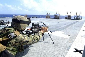 A U.S. marine adjusting his gun during target practice on an aircraft carrier.